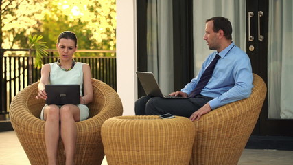 Business couple talking and comparing data on laptop on terrace