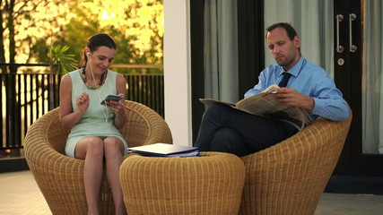 Business couple listening to music and reading newspaper on terr
