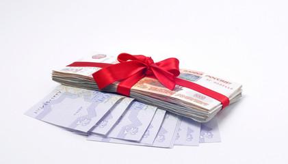 Стопка денег перевязанная красной подарочной лентой