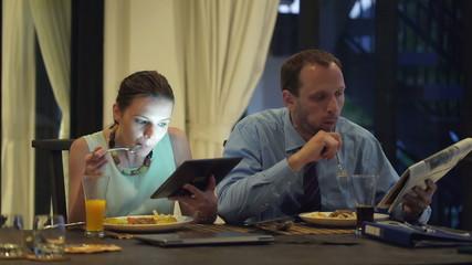 Business couple with tablet computer and newspaper eating dinner