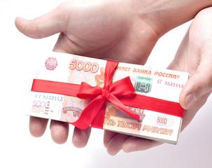Стопка денег перевязанная красной подарочной лентой в руках