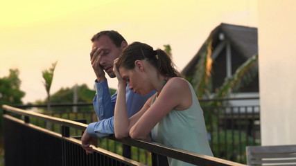Sad, tired business couple talking on terrace in the evening