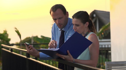 Business couple working with smartphone and documents on terrace