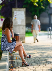 A young beautiful woman sitting in the park and looking at passe