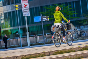 A young woman with ginger hair cycling in the street