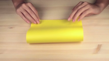 woman's hands make origami boat with yellow paper on wood table