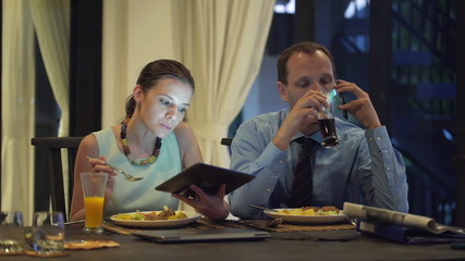 Business couple talking on cellphone, using tablet during dinner