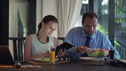 Business couple with tablet computer putting and eating salad at