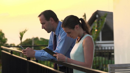 Business couple using tablet computer and smartphone on terrace