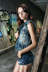 Fashion woman model posing near graffiti wall