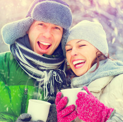 Happy winter couple having fun outdoors. Hot drinks