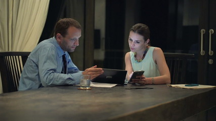 Business couple talking and working on tablet computer and smatp