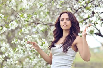Beautiful young brunette woman in blooming garden