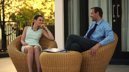 Business couple talking and relaxing on terrace