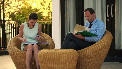 Business couple writing in documents and using smartphone on ter