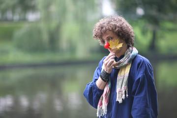 Romantic clown portrait with yellow maple-leaf
