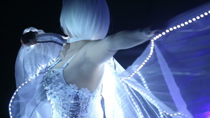 girl in white clothes and unusual white wigs dancing with LED