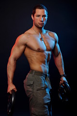 Muscular man poses with dumbbells on the dark background