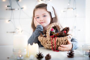 Wonderful girl with basket full of Christmas decoration.