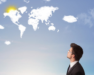 Businessman looking at world clouds and sun on blue sky