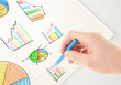 canvas print picture - Business person drawing colorful graphs and icons on paper