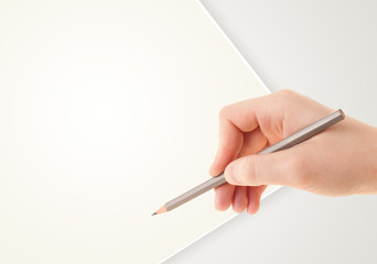 Human hand drawing with pencil on empty paper template
