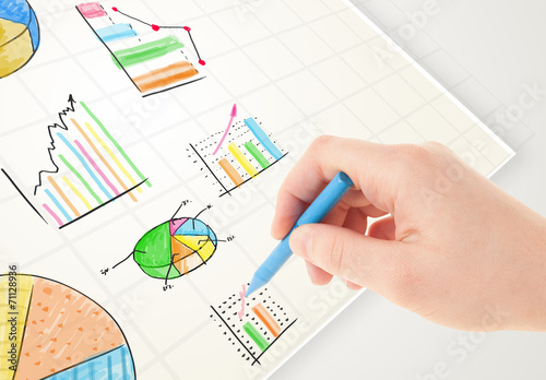 canvas print picture Business person drawing colorful graphs and icons on paper