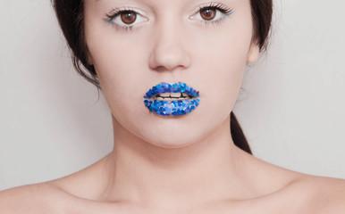 Девушка с блестящими синими губами на светлом фоне