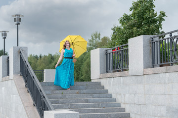 Beautiful girl in a blue dress with a yellow umbrella down the m