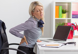 Woman having back pain while sitting at desk in office - 71130339