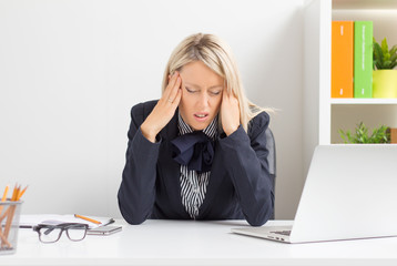 Woman having headache while sitting at desk in office