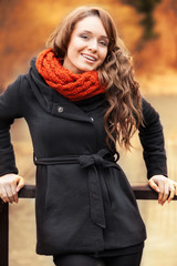 Smiling woman standing in autumn scenery