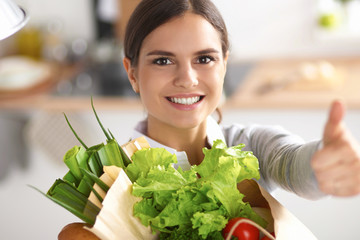 Young woman holding grocery shopping bag with vegetables and sh