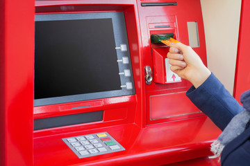 Woman inserting credit card into ATM to withdraw money