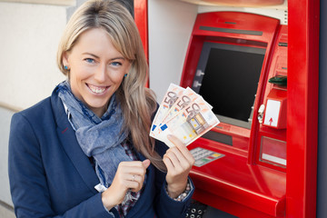 Happy woman withdrawing cash from ATM