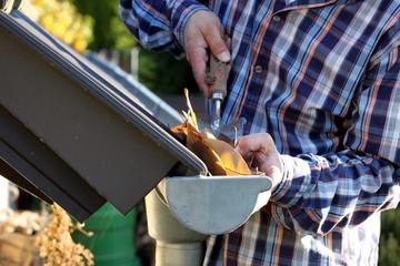 Handwerker reinigt Regenrinne von Herbstblättern