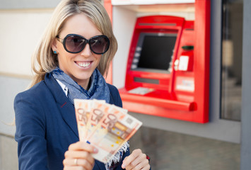 Happy woman withdrawing money from ATM