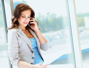Portrait of young businesswoman talking on mobile phone on offi