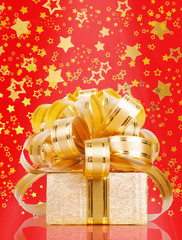 Gift box in gold wrapping paper on a beautiful red abstract back