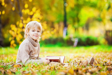 Boy is reading a book outdoors