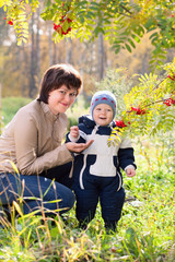 young mother woman girl and baby kid son on autumn background
