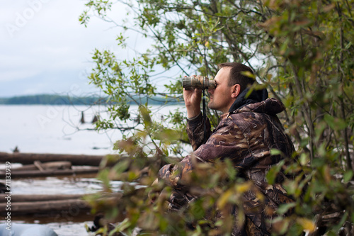 hunter looking through binoculars on the river - 71133939