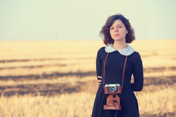 Beautiful brunette girl with camera on the countryside field