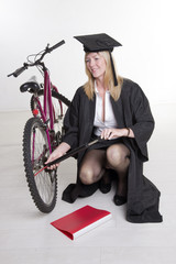 university student in cap and gown pumping cycle tyre