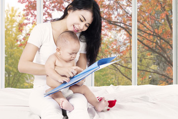 Baby read story book with mother
