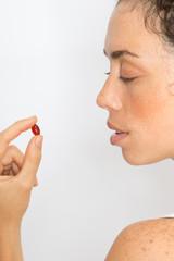Frau nimmt rote Tablette ein