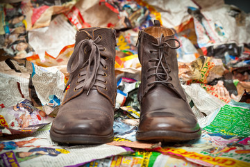 Men's leather boots standing next to crumpled scraps of paper