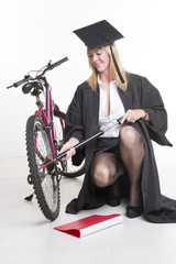 university student in cap and gown pumping bicycle tyre