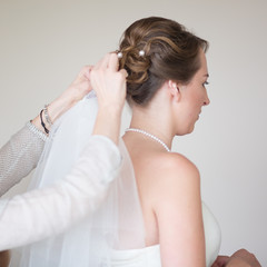 Young bride getting dressed for wedding