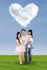 Cheerful family under cloud shaped heart